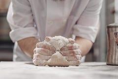 El panadero amasa la pasta en la tabla en la panader?a fotos de archivo