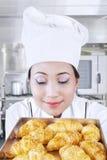El panadero asiático huele el pan Foto de archivo