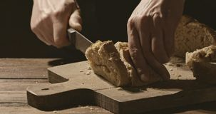 El panadero corta un pedazo de pan con una corteza curruscante en una tabla de cortar almacen de video