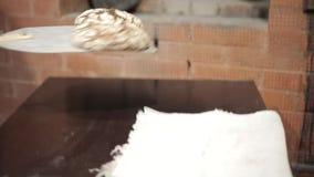 El panadero de sexo masculino en delantal sale de las barras de pan del horno dos almacen de metraje de vídeo