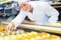 El panadero mayor feliz con el dulce se apelmaza en confitería local imagenes de archivo