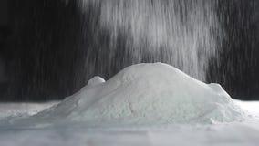 El panadero tamiza la harina a través de un tamiz Caídas de la harina de trigo en la tabla Ingrediente para hacer talud de torta metrajes