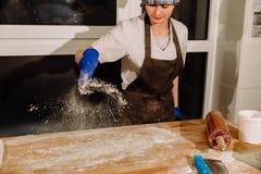 El panadero vierte la harina en la tabla Imágenes de archivo libres de regalías