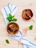 El panal y la miel en cuenco de madera con la hierbabuena pusieron en whi Fotos de archivo libres de regalías