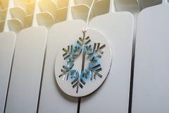 El panel blanco del radiador con un copo de nieve coronado de nieve simbólico imagenes de archivo
