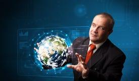 El panel de alta tecnología conmovedor de la tierra 3d del hombre de negocios Imágenes de archivo libres de regalías