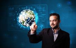El panel de alta tecnología conmovedor de la tierra 3d del hombre de negocios joven Imagen de archivo libre de regalías