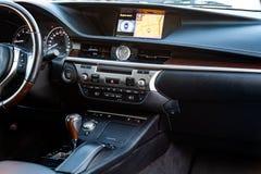 El panel de consola central dentro de un coche negro con las piezas de madera y del cromo, el navegador y los botones del control imagen de archivo libre de regalías