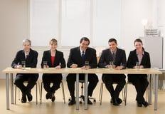 El panel de los compañeros de trabajo alrededor para conducir una entrevista Foto de archivo libre de regalías