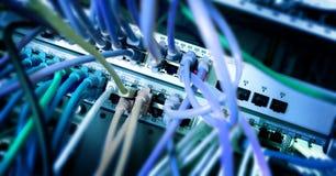 El panel del servidor de red con el cable de Ethernet colorido en los interruptores en un sistema escolar imagen de archivo libre de regalías