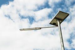 El panel solar con la iluminación en espacio de la nube y del cielo azul Imagen de archivo libre de regalías