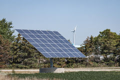 El panel solar con la turbina de viento en la distancia imagen de archivo libre de regalías