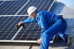 El panel solar del montaje del electricista en el tejado de la casa moderna fotos de archivo libres de regalías