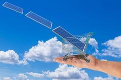 El panel solar en carro de la carretilla de las compras en la mano de las mujeres con el photovoltaics que baja del cielo fotografía de archivo