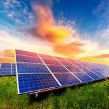 El panel solar en fondo anaranjado hermoso del ocaso fotos de archivo
