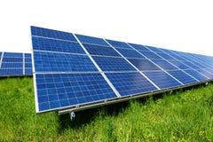 El panel solar en la hierba verde aislada en el fondo blanco Imágenes de archivo libres de regalías