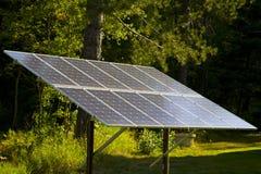 El panel solar en un rayo de sol del bosque Fotografía de archivo libre de regalías