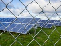El panel solar o granja fotovoltaica detrás de la cerca de chainlink del metal en campo verde con el cielo nublado dramático en A Imagenes de archivo