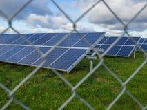 El panel solar o granja fotovoltaica detrás de la cerca de chainlink del metal en campo verde con el cielo nublado dramático en A Fotos de archivo libres de regalías