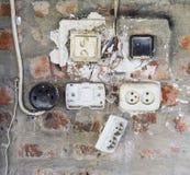 El panel viejo con los interruptores y los zócalos Viejo cableado eléctrico Imagen de archivo