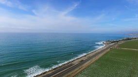 El panorama aéreo tiró de campo y de la carretera de maíz con tráfico de coche y el Océano Pacífico almacen de video