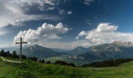 El panorama de la montaña con una vista magnífica de las montañas y los valles suizos y una cumbre cruzan fotografía de archivo libre de regalías