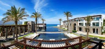 El panorama de piscinas y de la playa en el hotel de lujo Imagenes de archivo