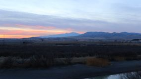 El panorama de un río en la oscuridad con una puesta del sol más allá de las montañas distantes enfoca como las cacerolas de la c almacen de metraje de vídeo