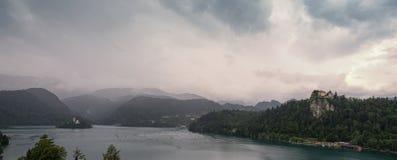 El panorama de una mañana gris y terrible en las montañas alpinas en el lago sangró foto de archivo
