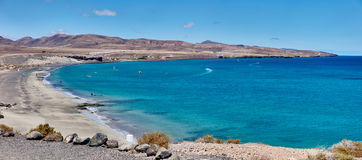 El panorama sobre la playa tropical, el agua azul del océano y el cielo azul en el paraíso de Fuerteventura ajardinan Imagenes de archivo