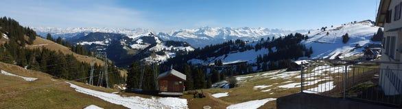 El panorama tiró de las montañas de la nieve en un día claro de la montaña Rigi Imagenes de archivo