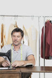 El paño de costura de la modista de sexo masculino en la máquina de coser con ropa atormenta en fondo Fotografía de archivo