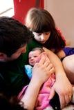 El papá acuna a la hermana grande recién nacida Looks On Fotografía de archivo