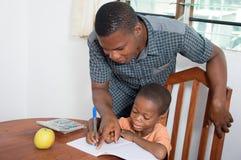 El papá ayuda a su niño a escribir àa casa Imágenes de archivo libres de regalías