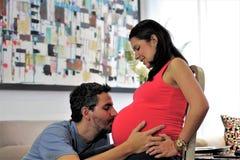 El papá besa el vientre embarazada del ` s de la esposa Imágenes de archivo libres de regalías