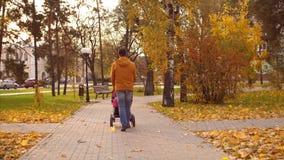 El papá camina con el cochecito en parque del otoño Cámara lenta almacen de video
