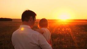 El papá camina con el pequeño niño en sus brazos en parque de la tarde en caída en la puesta del sol El papá y la hija pasan un d