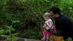 El papá camina con su hija en el bosque