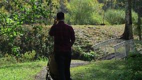 El papá camina con un cochecito en el parque almacen de metraje de vídeo