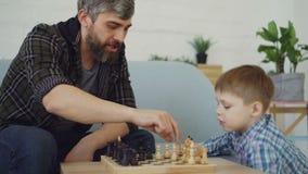 El papá cariñoso está jugando a ajedrez con su pequeño niño, le está enseñando a reglas y está hablando con él Criar a los niños, almacen de metraje de vídeo