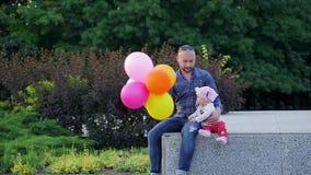 El papá con los globos coloridos en sus manos y con su hija linda se sienta en la repisa concreta en parque ilustrado de la ciuda almacen de metraje de vídeo