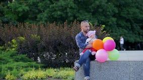 El papá con los globos coloridos en sus manos y con su hija linda se sienta en la repisa concreta en parque ilustrado de la ciuda metrajes