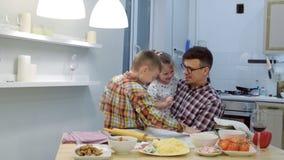 El papá con los niños cocina la pizza junta en la cocina metrajes