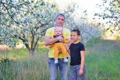 El papá con su hijo y la hija en una floración cultivan un huerto Imagenes de archivo