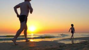 El papá corre después del niño a lo largo de la costa de mar en la puesta del sol almacen de video