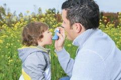 El papá da el inhalador para los problemas del sistema respiratorio Imagen de archivo