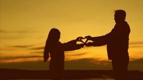 El papá da a su pequeña hija un símbolo del corazón en la puesta del sol Concepto de familia feliz El padre de amor estira la sil almacen de metraje de vídeo