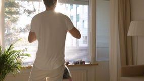 El papá da vuelta y lanza para arriba a la pequeña hija en las manos en el cuarto soleado Cámara lenta almacen de video