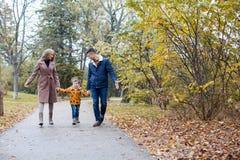 El papá de la mamá y un niño pequeño caminan en el parque fotos de archivo