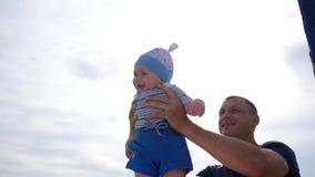 El papá educó al bebé en brazos, niño en manos fuertes del ` s del padre en luz del sol, niño en las manos del papá en el cielo a almacen de video